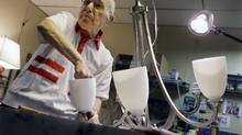 """Lighting repair specialistHerman """"Hy"""" Goldman, 101, refurbishes a light fixture in his workshop at Capitol Lighting where he has worked for 73 years, Monday, Aug. 18, 2014, in East Hanover, N.J. (AP)"""