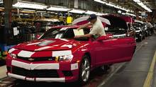 Workers at the General Motors plant in Oshawa work on a Camaro. (Moe Doiron/The Globe and Mail)