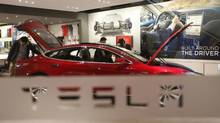 A man looks around Tesla Motors' Model S P85 at its showroom in Beijing on Jan. 29, 2014. The electric car maker is teaming up with Panasonic to build a $5-billion (U.S.) battery plant in the United States. (Kim Kyung Hoon/Reuters)