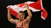 Gold medalist David Tremblay waves the national flag of Canada as he celebrates after defeating Bajrang Bajrang of India in their men's 61 kg gold medal wrestling bout at the Commonwealth Games Glasgow 2014, in Glasgow, Scotland, Wednesday, July, 30, 2014. (Alastair Grant/AP)