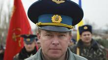Colonel Yuri Mamchur, commander of the Ukrainian garrison at the Belbek air base, leads his men to the base, outside Sevastopol, Ukraine, on Tuesday, March 4, 2014. Russian troops, who had taken control over Belbek airbase, fired warning shots in the air as around 300 Ukrainian officers marched towards them to demand their jobs back. (Ivan Sekretarev/AP)