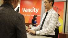"Vancity teller Tim Lu helps a client at the company's head office in Vancouver in this file photo. Vancity has a new product, the 'Fair & Fast Loan."" (Lyle Stafford For The Globe and Mail)"