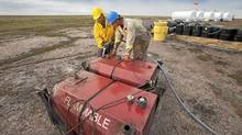 Two local men work at the fuel storage site at the proposed Kiggavik uranium mine, near Baker Lake, Nunavut. (THE CANADIAN PRESS/THE CANADIAN PRESS)