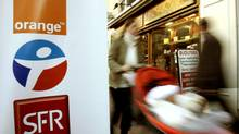 A woman passes by a display showing the logo of Orange SA in Nice, France. (ERIC GAILLARD/REUTERS)