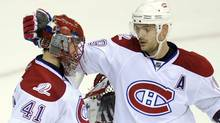 Montreal Canadiens goalie Jaroslav Halak (41), of Slovakia, and Andrei Markov, top right, of Russia, celebrate a 2-1 win as Washington Capitals left wing Alex Ovechkin (8), also of Russia, skates away in Game 5 of the NHL hockey playoffs, Friday, April 23, 2010, in Washington. (AP Photo/Nick Wass) (Nick Wass)