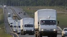 A convoy of white trucks carrying humanitarian aid passes along the main road M4 (Don highway) Voronezh region, Russia, Tuesday, Aug. 12, 2014. (Pavel Golovkin/AP)