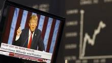 A TV screen showing U.S. President-elect Donald Trump is pictured in front of the German share price index, DAX board, at the stock exchange in Frankfurt, Germany, November 9, 2016. (© Kai Pfaffenbach / Reuters)
