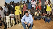 A photo of Canadian author Jay Bahadur posing with Somali villagers in Dhanane, the semiautonomous region of Puntland, Somalia, while researching a book about piracy in June 2009. The Somali pirates were nervous. A rookie author ? a white man from Canada ? had unexpectedly arrived in their cliff-top village to ask about the captured ship anchored offshore. Locals fearing a showdown quietly melted away into a small collection of shacks. (The Associated Press/The Associated Press)