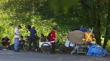 A cluster of homeless people gather on the side of a road near a treed area where city officials spread a load of chicken manure in an effort to keep them from living and sleeping in Abbotsford, B.C. (Jeff Vinnick For The Globe and Mail)