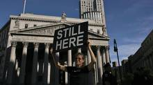 An Occupy Wall Street protester holds up a banner during activities organized by the movement 'OWS' New York City on Sunday, Sept. 16, 2012. (EDUARDO MUNOZ/REUTERS)