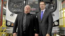Toronto Mayor Rob Ford, left, and Ontario Premier Dalton McGuinty, right, pose in front of a new subway car following a joint transit funding announcement at the Wilson car yard in Toronto, March 31, 2011. (J.P. MOCZULSKI/J.P. MOCZULSKI)