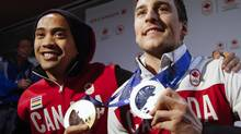 Long track speed skaters Denny Morrison, right, and Gilmore Junio arrive home from the Sochi Olympics in Calgary, Alta., Tuesday, Feb. 25, 2014. (Jeff McIntosh/THE CANADIAN PRESS)