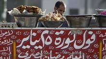 "A street vendor sells bean sandwiches, with a sign which reads ""Beans of 25 January Revolution"", at Tahrir Square in Cairo March 14, 2012. (AMR ABDALLAH DALSH/REUTERS)"