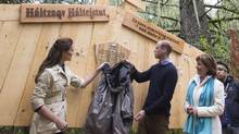The Duke and Duchess of Cambridge remove a rain jacket to unveil a plaque in the Great Bear rainforest in Bella Bella, B.C., Monday, Sept 26, 2016. (JONATHAN HAYWARD/THE CANADIAN PRESS)
