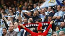 Manchester United supporters, with their triumphant red, show their rivalry with Manchester City fans, showing off their blue pennants. Sunday's derby is at Etihad Stadium, Manchester City's home. (Phil Noble/REUTERS)