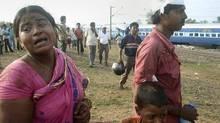 Passengers stand with others at the scene of a train crash near Sardiha, about 150 kilometres west of Calcutta. (Samir Mondal/Samir Mondal/AP)