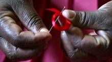 A Kenyan woman prepares ribbons ahead of World Aids Day at Beacon of Hope centre, a non-government organization formed to address women's problem of HIV/AIDS in Nairobi, November 25, 2004. (© Antony Njuguna / Reuters/REUTERS)