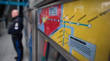 A Canada Line map is seen on a ticket machine as a Metro Vancouver Transit Police officer stands by at Richmond-Brighouse Station in Richmond, B.C. (Darryl Dyck for The Globe and Mail)