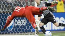 Toronto FC forward Ali Gerba falls as he attempts to shoot against River Plate goalkeeper Daniel Vega during a friendly match in Toronto on Wednesday July 22, 2009. (FRANK GUNN)