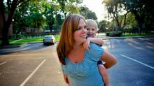 Penny Stamp, with her two-year-old son Charlie Burgess, take a walk in her neighbourhood in Orlando, Fla. Ms. Stamp was born in Regina and raised in Toronto. (Roberto Gonzalez for The Globe and Mail)