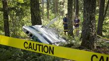 June 30, 2013: Long weekend campers Brad and Kirstin Hallet survey a wing of a Cessna plane that was involved in a mid-air collision with a glider near Pemberton Saturday. The couple was camping at Nairn Falls at the time of incident in which four people died. (BONNY MAKAREWICZ For the Globe and Mail)