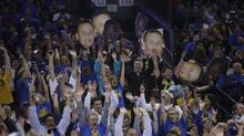 Fans do the wave as the Golden State Warriors jump ahead of the Memphis Grizzlies during the second half of an NBA basketball game in Oakland, Calif., on April 13, 2016. (Marcio Jose Sanchez/THE ASSOCIATED PRESS)