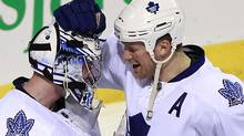 Toronto Maple Leafs goalie James Reimer (34) is congratulated on his win against the Montreal Canadiens by teammate Mike Komisarek (8) following third period NHL hockey action in Montreal, February 24, 2011. REUTERS/Christinne Muschi (CHRISTINNE MUSCHI)
