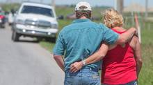 A couple from High River walk back to their pick-up truck after they listened to a live press conference which announced re-entry plans to their flooded town. Some residents of High River can return to their homes tomorrow (Saturday, June 29), and others will be able to tour the community by bus, said Rick Fraser, the Associate Minister of Regional Recovery and Reconstruction for High River (Chris Bolin for The Globe and Mail)