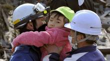 A little child is held by rescue workers after being rescued from a building at Kesennuma, northeastern Japan, on Saturday March 12, 2011. (Kyodo News/AP/Kyodo News/AP)