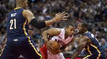 Toronto Raptors guard Kyle Lowry, centre, drives through Indiana Pacers teammates David West (21) and Lavoy Allen (2) during first half NBA basketball action in Toronto on Dec. 12, 2014. (Nathan Denette/The Canadian Press)