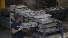 Rick Keleher picks up moulded bricks of raw material before they are flash moulded at ABS Friction brake pad manufacturing facility in Guelph, Ont., on June 9, 2014. (Pawel Dwulit for the Globe and Mail)