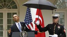 U.S. President Barack Obama checks to see if he still needs the umbrella held by a U.S. Marine to protect him from the rain during a joint news conference with Turkish Prime Minister Recep Tayyip Erdogan in the Rose Garden of the White House in Washington, May 16, 2013. (JASON REED/REUTERS)
