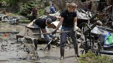 Residents shovel layers of mud flood debris in Calgary, Alberta June 25, 2013. Officials said about 65,000 Calgary residents had now returned to the houses they left on Friday after the Bow and Elbow rivers spilled their banks. (ANDY CLARK/REUTERS)