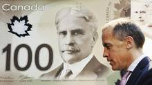 Mark Carney, governor of the Bank of Canada and chairman of the Financial Stability Board, walks past a replication of the new Canadian 100 dollar bill made of polymer in Toronto November 14, 2011. (Mark Blinch/Reuters)