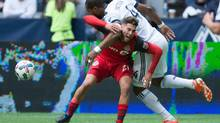 Toronto FC midfielder Jonathan Osorio and Vancouver Whitecaps defender Kendall Waston vie for the ball during an MLS soccer game in Vancouver on Saturday, March 18, 2017. (DARRYL DYCK/THE CANADIAN PRESS)