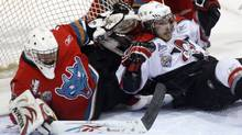Kelowna Rockets goaltender Mark Guggenberger braces himself for a collision with Gabriel Dumont of the Drummondville Voltigeurs during preliminary round play at the Memorial Cup. (Ryan Remiorz/CP)