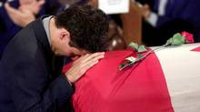 Justin Trudeau cries has he kneels before the casket of his father, former Canadian prime minister Pierre Trudeau, after the reading of the eulogy on Oct. 3, 2000, in Montreal. (PAUL CHIASSON/AFP PHOTO)