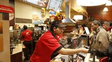 Staff serve customers at a Tim Hortons on Queen St., Toronto, on Feb. 20, 2014. (Fernando Morales/The Globe and Mail)