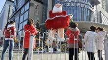 Women take pictures of a Santa Claus figure outside a shopping mall in Taiyuan, Shanxi province, earlier this month. The torrid pace of growth has raised Chinese living standards and has created a burgeoning consumer class. (JON WOO/REUTERS)