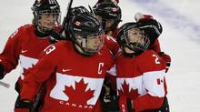 Meghan Agosta-Marciano of Canada (2) is congratulated by Caroline Ouellette (13) after scoring a goal against Finland during the third period of the 2014 Winter Olympics women's ice hockey game at Shayba Arena, Monday, Feb. 10, 2014, in Sochi, Russia. (Petr David Josek/AP)