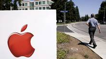 A worker walks towards Apple headquarters in this file photo. Apple is now the biggest stock on the S&P 500 and has been seen as a safe haven for investors in rocky markets. (AP Photo)