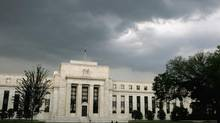 Storm clouds gather over the U.S. Federal Reserve Building in Washington. (JIM BOURG/REUTERS)