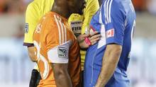 Houston Dynamo midfielder Corey Ashe (26) has words with Montreal Impact forward Marco Di Vaio (9) after a hard foul in the first half as referee Mark Geiger steps in during a knockout-round match in the MLS Cup soccer playoffs, Thursday, Oct. 31, 2013, in Houston. (BOB LEVEY/AP)
