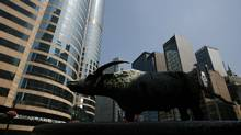 A statue of a bull is seen outside Exchange Square (L), where the trading hall of the Hong Kong Stock Exchange is located, May 24, 2010. (Bobby Yip/Reuters/Bobby Yip/Reuters)