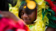 Ashley Scantlebury peeks out from behind a feathered headdress at the media launch for the Junior Carnival Parade and Family Day, July 9, 2012. (Galit Rodan/The Globe and Mail)