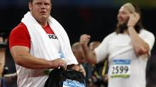 Canada's Dylan Armstrong, left, from Kamloops, B.C., packs his bag as gold medal winner Tomasz Majewski, from Poland, celebrates the shot put final at the 2008 Summer Olympics in Beijing, Friday, August 15, 2008. (Ryan Remiorz/The Canadian Press)