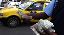 A fuel attendant handles Kenyan shilling notes at a petrol station in the capital Nairobi March 15, 2011. (NOOR KHAMIS)