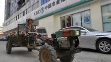 A farmer drives a tractor past a branch of Agricultural Bank of China in Xiangfan, Hubei province, in this 2010 picture. (© Stringer Shanghai / Reuters/Reuters)