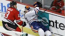 Chicago Blackhawks winger Daniel Carcillo boards Edmonton Oilers defenceman Tom Gilbert on Jan. 2. (Charles Rex Arbogast/Associated Press/Charles Rex Arbogast/Associated Press)
