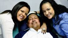 Venezuela's President Hugo Chavez smiles in between his daughters, Rosa (R) and Maria while recovering from cancer surgery in Havana in this file photograph released by the Ministry of Information on February 15, 2013. (HANDOUT/REUTERS)